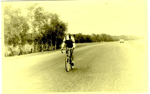 Велогонка «Союз». 1993 год. Игорь Иванников. Едет в отрыве на групповой гонке. Позади виднеется машина ГАИ и за ней пелетон.